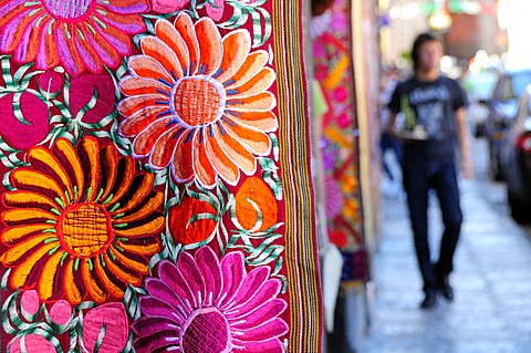 Mexico, Bajio, San Miguel de Allende, Brightly coloured embroidered textile hanging outside arts shop with flower design in pink red and orange.
