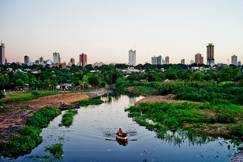 A fisherman rows his boat along polluted waters of La Chacarita slum within sight of towers at a developed area in Asuncion, Paraguay, April 19, 2013. An economic boom in Paraguay has made it the fastest-growing country in the Americas, yet much of the country remains mired in poverty. (Tomas Munita/The New York Times)