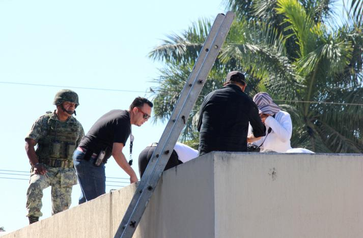 A soldier stands guard as forensic technicians work at a crime scene where the body of a man, who witnesses said was tossed from a plane, landed on a hospital roof in Culiacan, in Mexico's northern Sinaloa state April 12, 2017. REUTERS/Jesus Bustamante