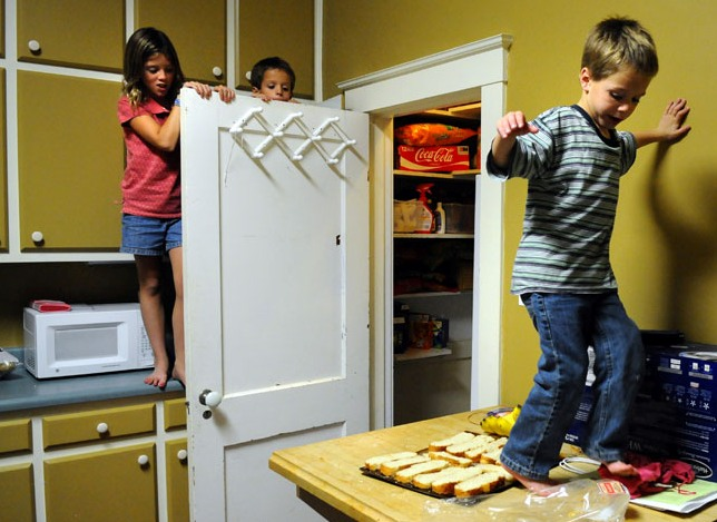 "Jaxsyn Wood, 5, is avoiding ""hot lava,"" which is a game he likes to play with his siblings in his family's Dannville home. Jackson, one of 11 children, was helping while the family was in the kitchen making dinner."