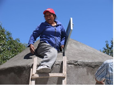 A campesina joyously tops off the rain-harvesting cistern her community developed with contributions from people like you!