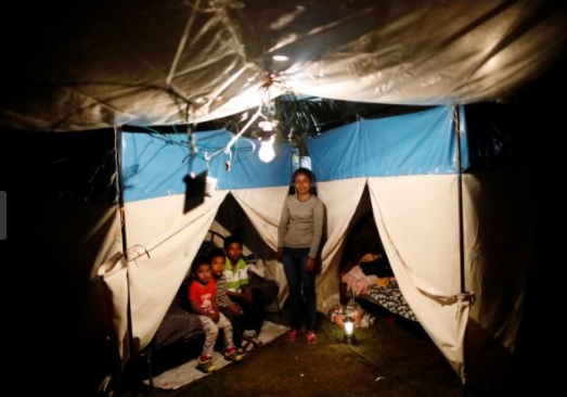 Veronica Dircio, 34, a housewife, poses for a portrait with her sons in front of a tent in a neighbour's backyard after an earthquake in San Juan Pilcaya, at the epicentre zone, Mexico, September 28, 2017. Dircio's house was badly damaged